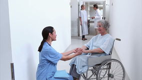 Nurse looking at a patient in a wheelchair Stock Footage