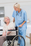 Nurse looking at senior patient sitting on wheelchair Royalty Free Stock Photography