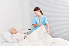 Nurse looks after a sick senior citizen. Nurse cares for a sick senior citizen in bed in nursing home or hospice stock images