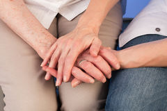 Nurse lovingly holds the hand of a senior woman. Nurse lovingly holds the hand of a senior women in homecare situation Stock Photo