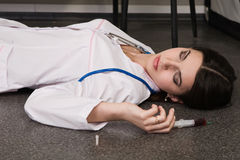 Nurse lying on the floor Stock Images