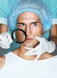 Nurse with magnifying glass near the face of the patient. Stock Image