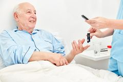 Blood glucose measurement in patients with diabetes. Nurse makes blood glucose measurement in senior as a patient with diabetes stock photo
