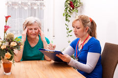 Nurse makes home visit and record data Royalty Free Stock Photo