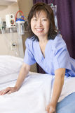 A Nurse Making A Bed Smiling Royalty Free Stock Photos