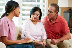 Nurse Making Notes During Home Visit With Senior Couple Royalty Free Stock Images