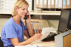 Nurse Making Phone Call At Nurses Station Stock Photos