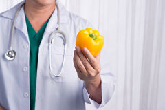 Nurse or male doctor giving bell pepper smiling. Health care con Stock Photos