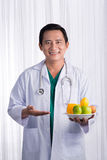 Nurse or male doctor giving fruits. Health care concept  Royalty Free Stock Photos