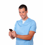 Nurse man texting and smiling at you Stock Photos