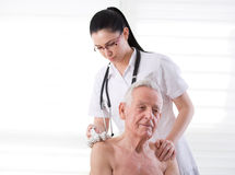 Nurse masagging old man with roller massager Stock Photos