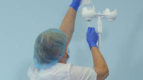 Nurse in mask and gloves preparing IV drip stand royalty free stock images