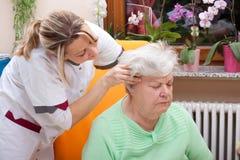 Nurse massages the head of a senior Royalty Free Stock Photos
