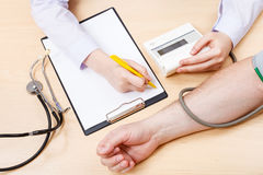 Nurse measures blood pressure of patient Stock Photos