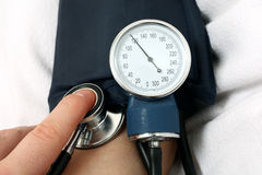 Nurse measuring the blood pressure Stock Photo