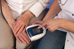 Nurse measuring blood pressure of an elderly woman. Nurse points at the display of a digital blood pressure gauge while measuring blood pressure of an elderly royalty free stock image