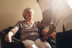 Nurse measuring blood pressure of her senior patient Stock Photo
