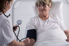 Nurse measuring blood pressure Stock Image