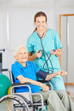 Nurse measuring blood pressure of old woman Stock Photos