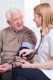 Nurse measuring blood pressure. Of senior man Stock Photos