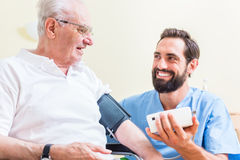 Nurse measuring blood pressure of senior patient Stock Photo