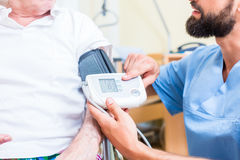 Nurse measuring blood pressure of senior patient Royalty Free Stock Images