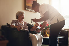 Nurse measuring blood pressure of senior patient in retirement h. Nurse measuring blood pressure of senior women patient in retirement home. Home caregiver doing Stock Photography