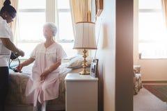 Nurse measuring blood pressure of senior woman Royalty Free Stock Photos