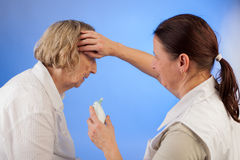 Nurse measuring fever at an elderly woman Stock Image