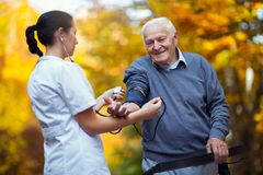 Nurse measuring old patient`s blood pressure Royalty Free Stock Photos