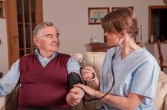 Nurse measuring senior's blood pressure stock photography