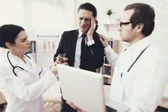 Nurse in medicine gown gives glass of water to successful businessman who has headache. stock images