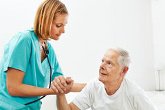 Nurse in nursing home helping senior man. Nurse in nursing home helping senior men getting up from bed royalty free stock photos