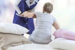 Nurse in nursing home helping senior woman getting up from bed in her bedroom stock photos