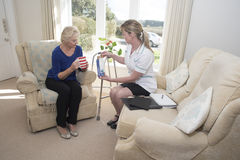 Nurse offering advice on drug taking. Health visitor with an elderly patient on a home visit giving advice on prescription drugs royalty free stock images