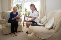 Nurse offering advice on drug taking. Health visitor with a patient on a home visit giving advice on prescription drugs stock images