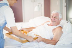 Nurse offering breakfast to senior man lying on bed Royalty Free Stock Images