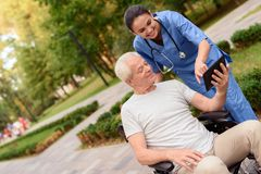 A nurse and an old man are looking at something on an old man`s tablet. An old men sitting in a wheelchair and a nurse with a stethoscope looking at something on Stock Image