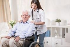 Nurse with old man on wheelchair stock photos