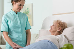 Nurse and older patient. Young pretty nurse and her older sick patient in hospital bed Royalty Free Stock Photography