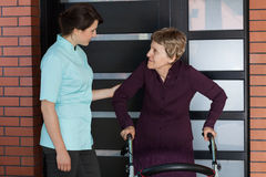 Nurse and older woman standing in front of house Royalty Free Stock Photos
