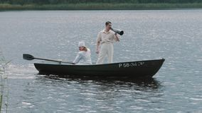 Nurse paddling boat on lake, man in hair net yelling into megaphone stock footage