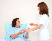A nurse and a patient. A nurse giving water and pills to a patient isolated on a white background Royalty Free Stock Photo