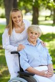 Nurse and patient. Pretty nurse and senior patient in a wheelchair looking at camera Stock Photo