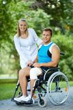 Nurse and patient. Pretty nurse walking with male patient in a wheelchair in park Stock Photography