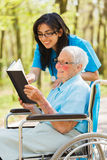 Nurse and Patient Reading Royalty Free Stock Image