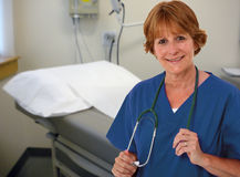 Nurse in Patient's Room. Nurse In Her 50's Holding Stethoscope Around Neck In Patient's Room Royalty Free Stock Image