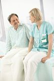 Nurse and patient sitting on bed Royalty Free Stock Images