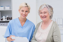 Nurse and patient smiling in clinic. Portrait of nurse and patient smiling in clinic Royalty Free Stock Photo