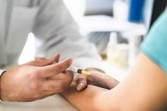 Nurse and patient taking blood test in doctor office room in hospital. stock photo